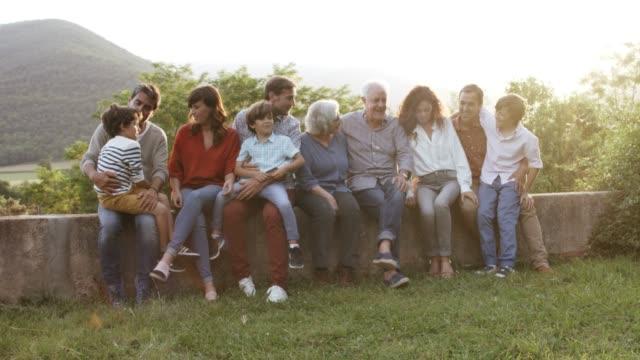 glücklich multi-generationen-familie sprechen in hof - geschwister stock-videos und b-roll-filmmaterial
