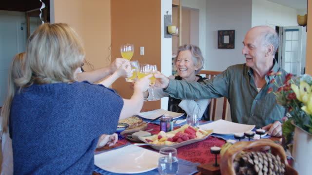 glücklich-generationen familie toast während der mahlzeit - esstisch stock-videos und b-roll-filmmaterial