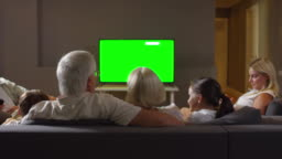 Happy Multigenerational Family Watching TV on Sofa and Chatting