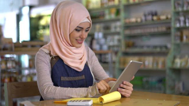 happy muslim business owner using a tablet and a notepad looking very satisfied and smiling - islam stock videos & royalty-free footage