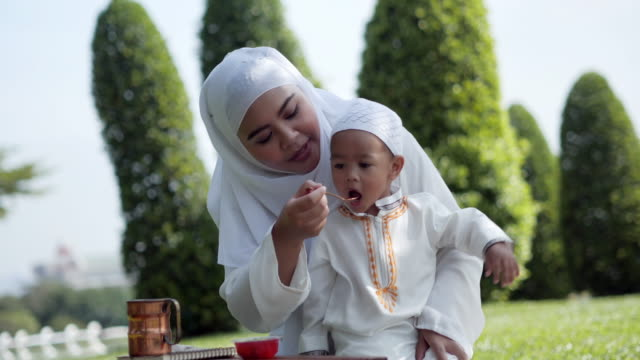 happy muslim family holidays. joyful mother and baby.son having a good time outdoors.muslim lifestyle concept - saudi arabia stock videos & royalty-free footage