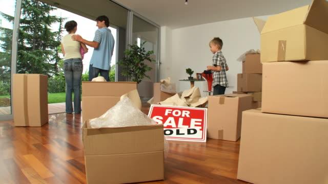 hd dolly: happy neue hausbesitzer - immobilienschild stock-videos und b-roll-filmmaterial