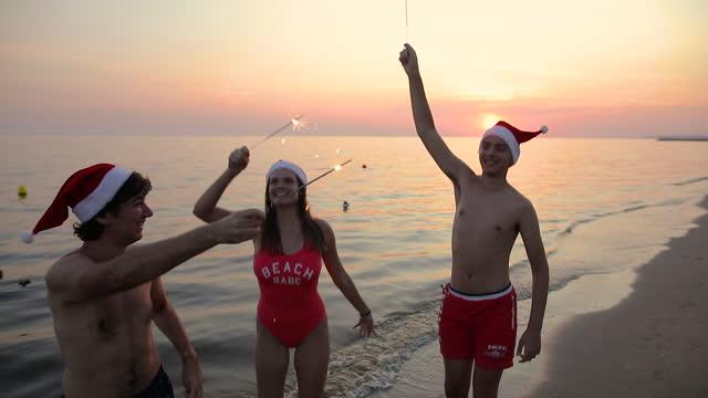 vidéos et rushes de bonne année, joyeuses fêtes, sparklers brillants dans les mains - party hat