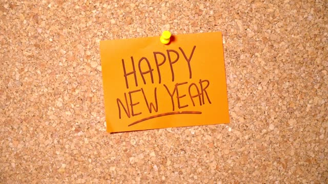 happy new year word group on paper pinning up on corkboard by a man - notice board stock videos and b-roll footage