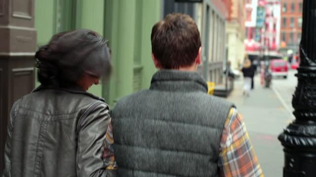 vídeos de stock, filmes e b-roll de happy new york couple laugh as they walk arm-in-arm down sidewalk in soho - de braços dados