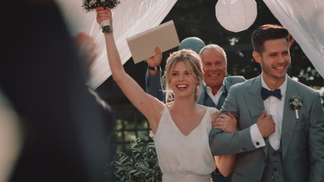 happy newlywed couple greeting guests in ceremony - arm in arm stock videos & royalty-free footage