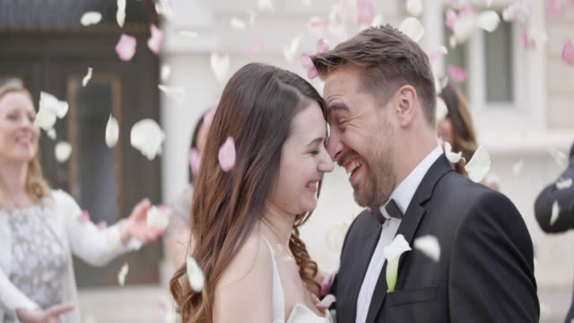 SLO MO Happy newlyweds in a rose petal shower