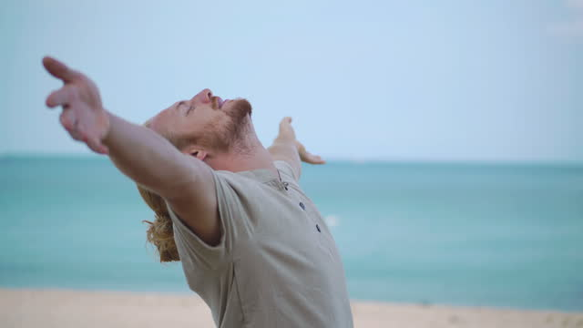 happy of freedom young men age 25 yearold of caucasian ethnicity raises arms into air while open arms enjoying travel holidays on the beach.open arms concept. - wonderlust stock videos & royalty-free footage