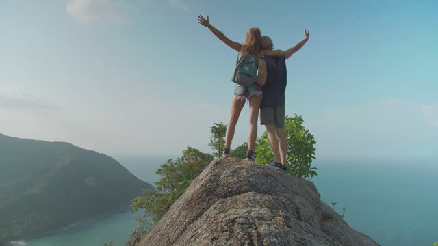 happy of travelers couple age 25-29 yearold of latin american and hispanic ethnicity raises arms into air while open arms enjoying travel holidays on top of mountain ocean summit together.open arms concept. - wonderlust stock videos & royalty-free footage