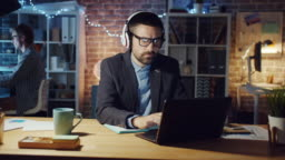 Happy office worker in headphones listening to music working with laptop at night