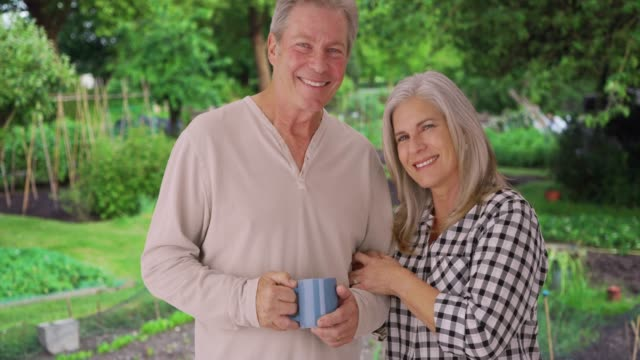 happy old caucasian couple stand together in lush green garden - altri temi video stock e b–roll