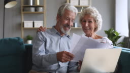 Happy old couple talking checking papers holding bills and laptop