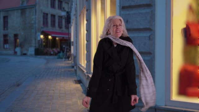 happy older woman dances on the street at night in the fall wearing black coat - senior women stock videos & royalty-free footage
