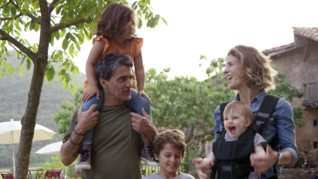 stockvideo's en b-roll-footage met gelukkige ouders genieten met kinderen in achtertuin - twee ouders