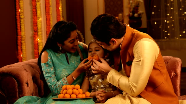 ms happy parents feeding laddoo to their daughter while sitting on sofa during diwali festival / delhi, india - sweet food stock videos & royalty-free footage