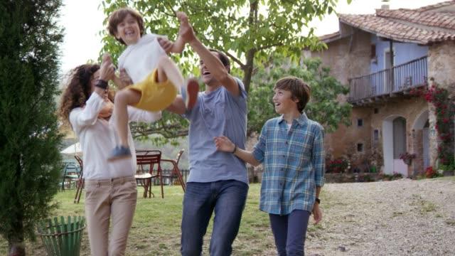 vídeos de stock e filmes b-roll de happy parents swinging son on footpath in backyard - cena não urbana