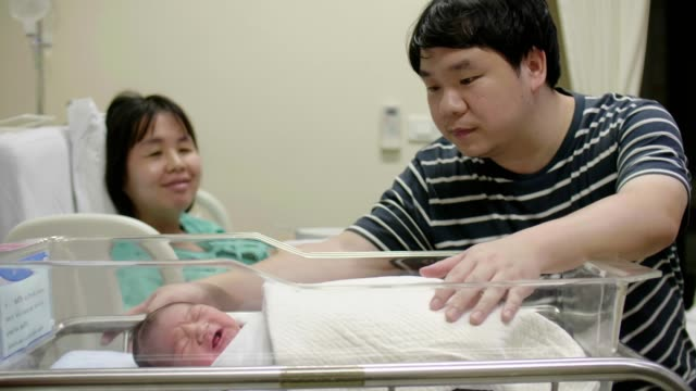 happy parents with newborn baby - delivery room stock videos & royalty-free footage