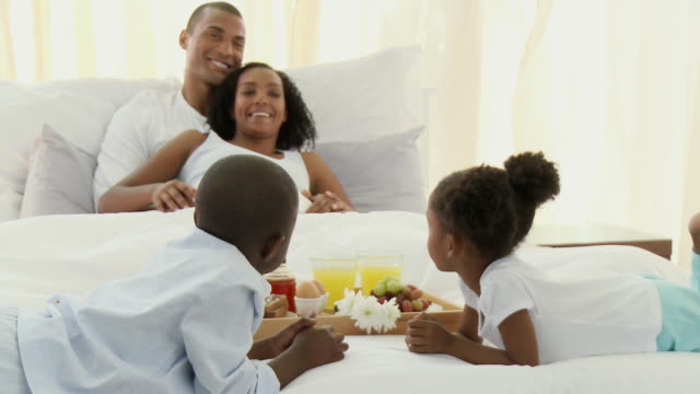 MS Happy parents with son and daughter (4-5) having breakfast in bed / Cape Town, Western Cape, South Africa