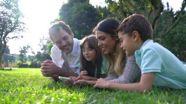 vídeos de stock, filmes e b-roll de pais felizes com seus dois miúdos que encontram-se em suas barrigas no parque que prestam atenção a vídeos no smartphone - parque público