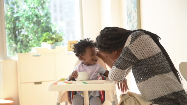 stockvideo's en b-roll-footage met happy playful black mother and daughter at feeding time in high chair - dreadlocks