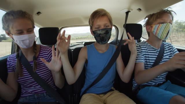 vídeos de stock, filmes e b-roll de crianças divertidas felizes viajando de carro durante a pandemia covid-19 - alegria