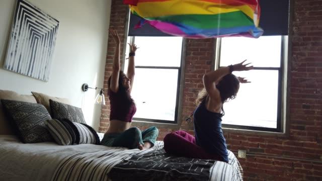 glada lekfulla kvinnor par thworing en regnbåge hbtq-flagga i luften - alternativ livsstil bildbanksvideor och videomaterial från bakom kulisserna