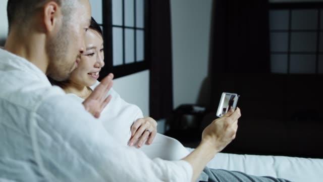 幸せな妊娠カップル ビデオ通話 - ズーム点の映像素材/bロール