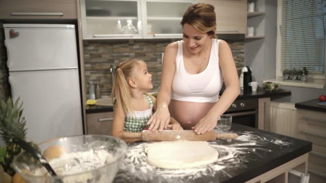 Glückliche schwangere Mutter und ihre kleine Tochter Kneten von Teig und Cookies in der Küche zu machen.