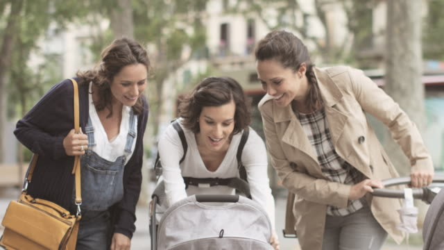 Happy pregnant woman and friends playing with baby