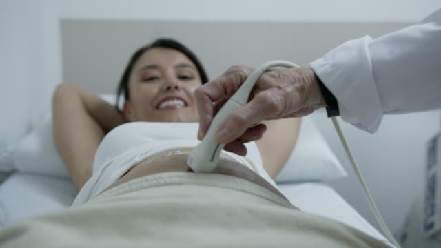 画面を見ながら笑顔超音波の予約で幸せな妊婦 - 人体点の映像素材/bロール