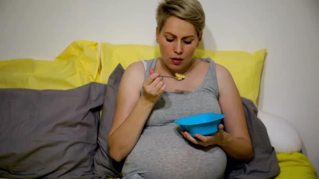 vidéos et rushes de heureuse femme enceinte manger salade de fruits pour le petit déjeuner à la maison - soin prénatal
