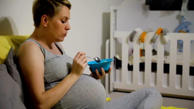 vídeos de stock e filmes b-roll de happy pregnant woman eating fruit salad for breakfast at home - comida e bebida