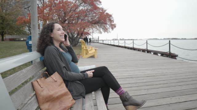 公園のベンチに座っている間、携帯電話で話す幸せな妊婦 - ユーラシアエスニシティ点の映像素材/bロール