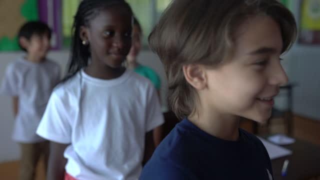 教室で机の横に立っている幸せな生徒たち。 - 消しゴム点の映像素材/bロール