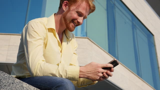 happy red-haired guy is using a smartphone in the city - redhead stock videos and b-roll footage