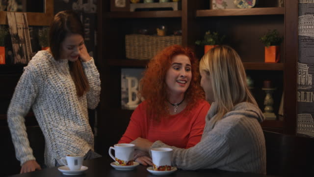 Happy redhead woman being surprised with gift box from her female friends.