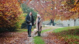 Happy Retired Senior Couple Taking Dog For Walk Along Path In Autumn Countryside Together