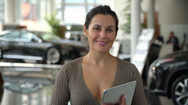 happy sales woman working at a car dealership smiling at camera - selling stock videos & royalty-free footage
