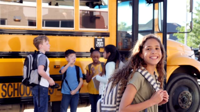 happy schoolgirl smiles cheerfully before boarding school bus - first day of school stock videos & royalty-free footage