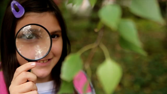 happy schoolgirl with magnifying glass - childhood stock videos & royalty-free footage