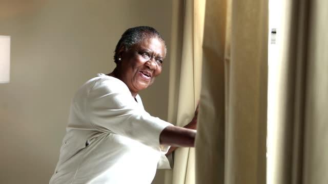 vidéos et rushes de femme aîné heureuse d'afro-américain regarde la fenêtre - salle attente