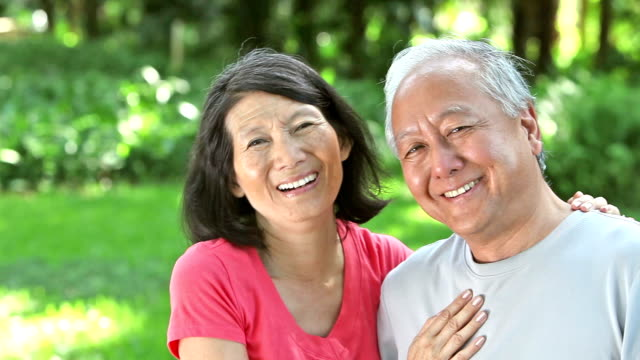 幸せなシニアアジアカップルの公園 - 年配のカップル点の映像素材/bロール
