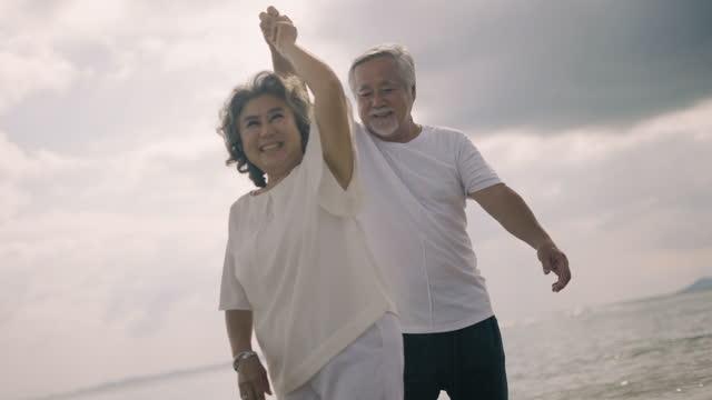 glückliches senior-paar tanzen und umarmen am strand - ehemann stock-videos und b-roll-filmmaterial