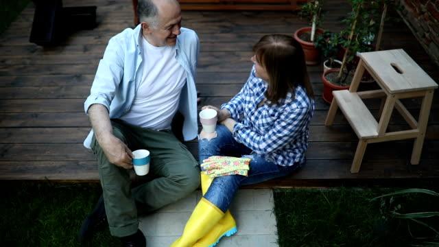 happy senior couple drinking coffee in the garden - gardening glove stock videos & royalty-free footage