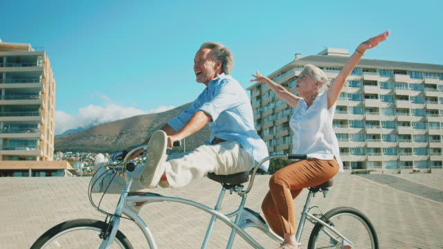 happy senior couple enjoying on tandem bicycle - telecamera traballante video stock e b–roll