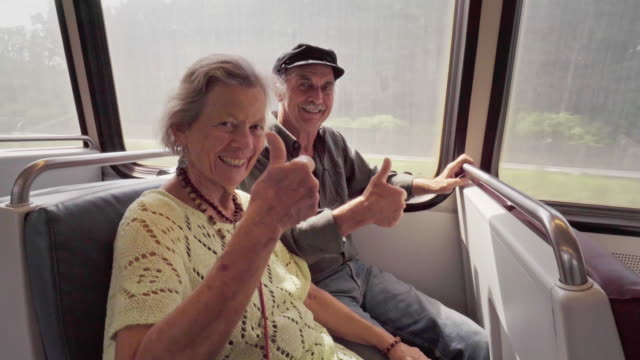 stockvideo's en b-roll-footage met gelukkige senior paar geven thumbs up signaal op een metro-trein - train vehicle