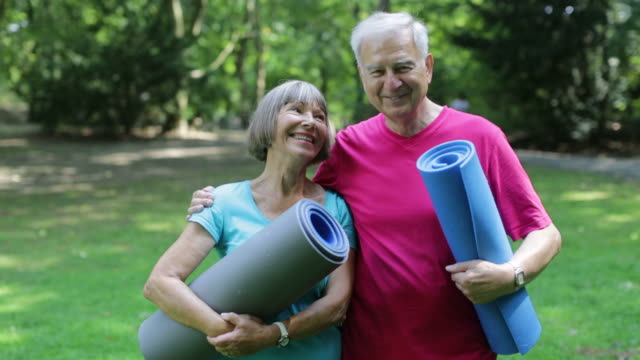Happy senior couple holding yoga mats in park