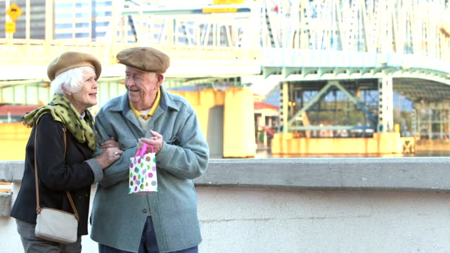 stockvideo's en b-roll-footage met gelukkige senior paar in warme kleding, wandelen, praten - 70 79 jaar