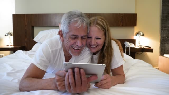 Happy senior couple lying in bed on their tummies watching a movie on a digital tablet laughing and having fun