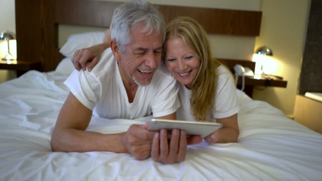 Happy senior couple lying on their tummies on the bed looking at photos on a digital tablet laughing and having fun